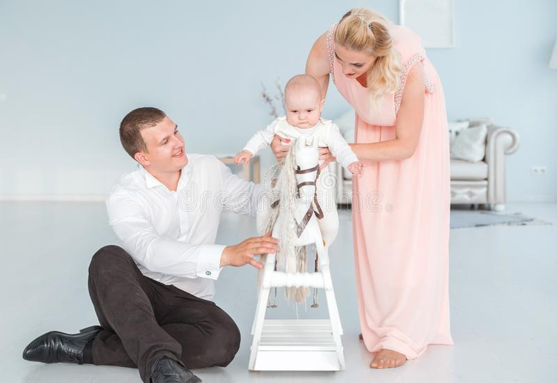 Mom and dad roll their little son on a children`s toy horse stock photography