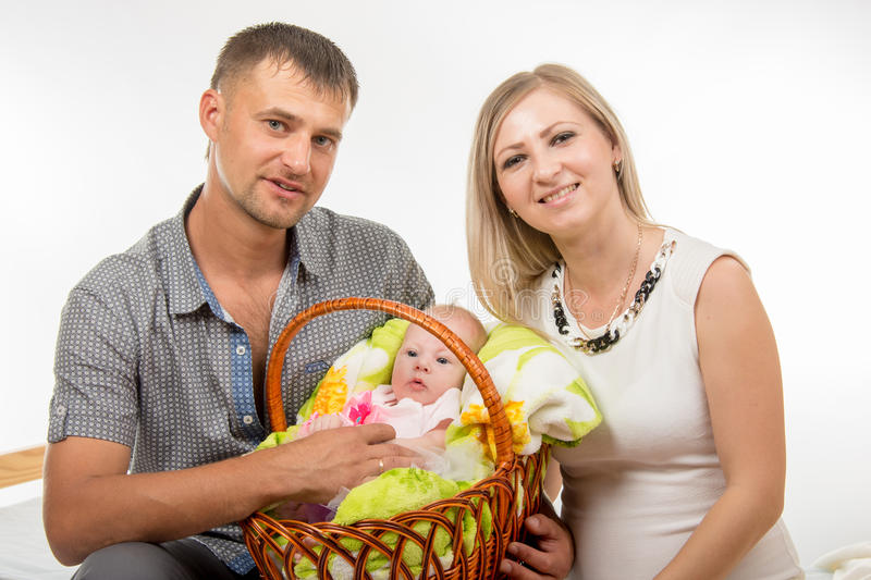 Mom and dad sit on the bed and holding a two-month baby girl in a basket. Young parents mom and dad sit on the bed and keep in the hands of his two-month newborn royalty free stock photography