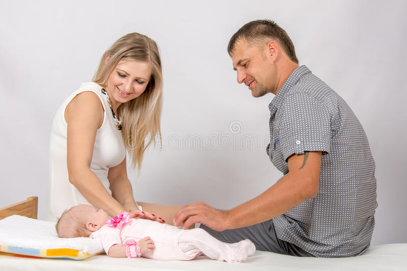 Mom and dad sit on the bed on which lay their baby. Young parents Mom and Dad sit at the crib, the crib on his back lying on the two-month girl royalty free stock photography