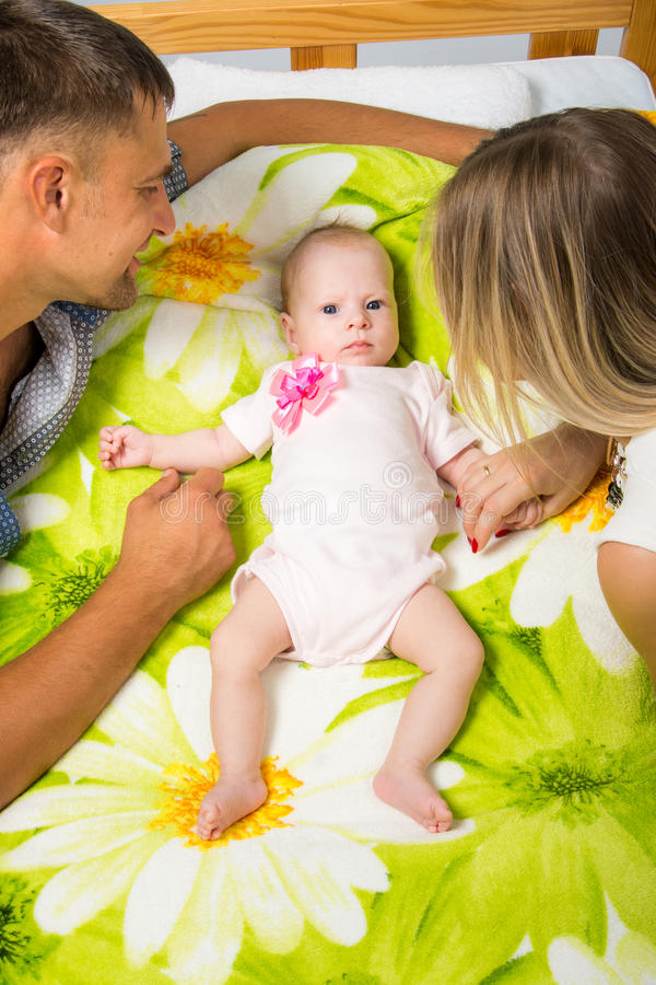 Mom and Dad are sitting around a two-month baby who is lying on the bed. Young parents Mom and Dad sit at the crib, the crib on his back lying on the two-month stock photos