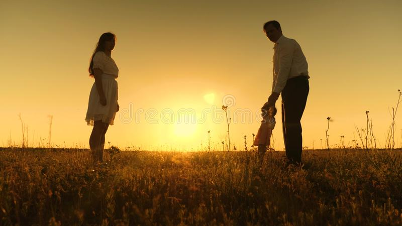 Mom and dad are taught to go to small daughter, young beautiful family in park with a child at sunset royalty free stock photos