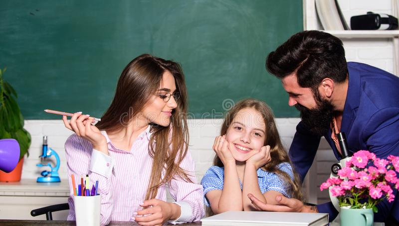 Mom and dad teachers helping child with learning. Smart family. Teaching daughter. Favorable conditions for learning royalty free stock photography