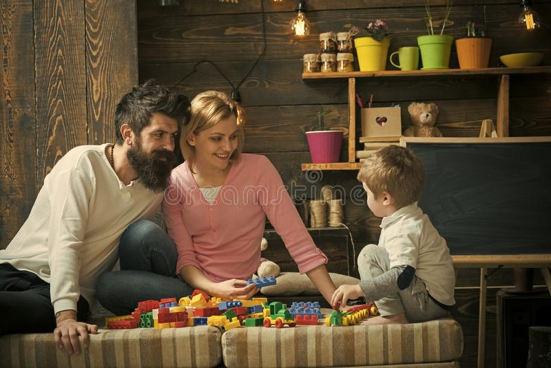 Mom and dad watch son playing with construction blocks. Side view blond kid sitting on the edge of sofa. Happy family in royalty free stock photography