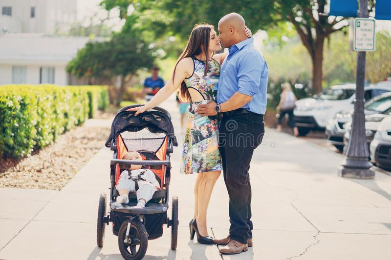 Family on a walk. Mom and dad a wonderful little son walking in summer sunny city royalty free stock images