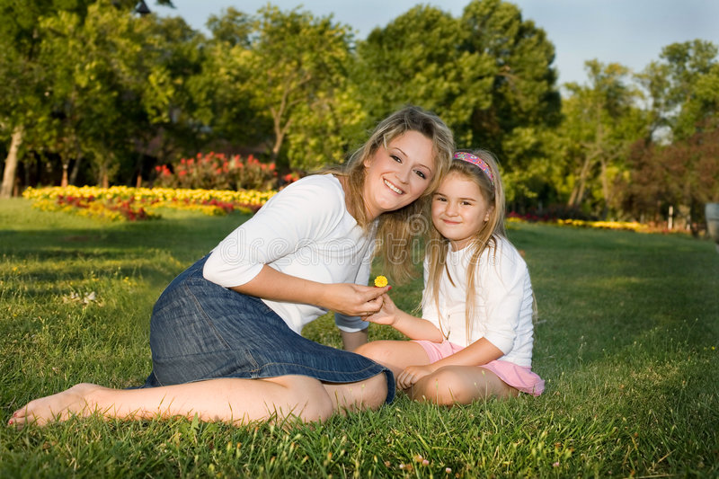 Mom and daughter. Mom and daugter sitting at the park royalty free stock photo