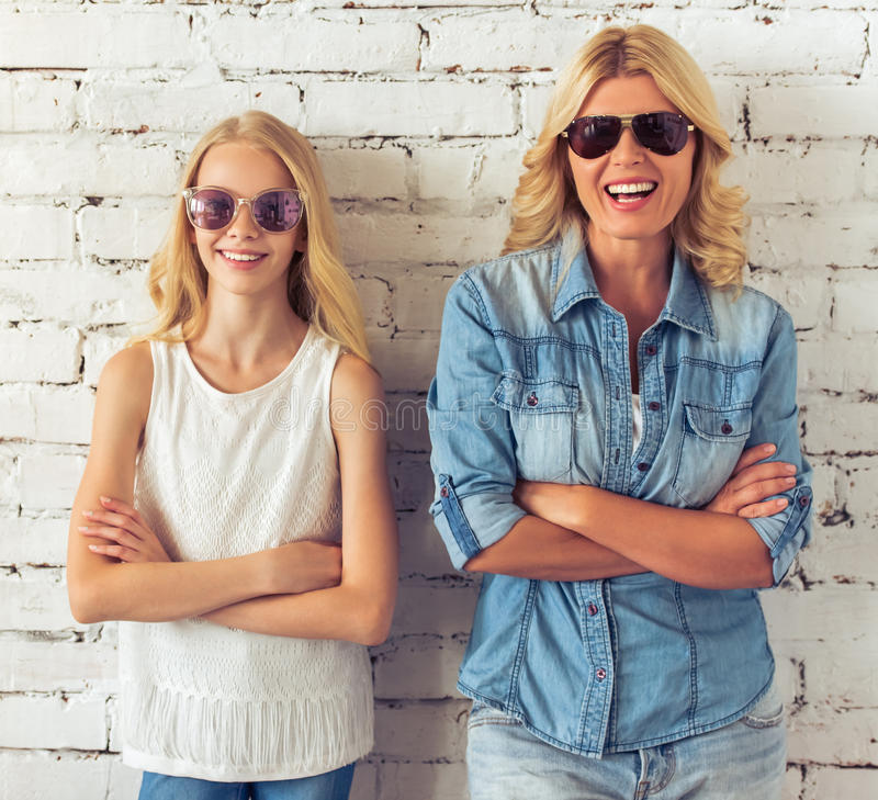Mom and daughter. Attractive blondes, teenage girl and her mother, in sun glasses are looking at camera and smiling, standing with crossed arms against white stock image