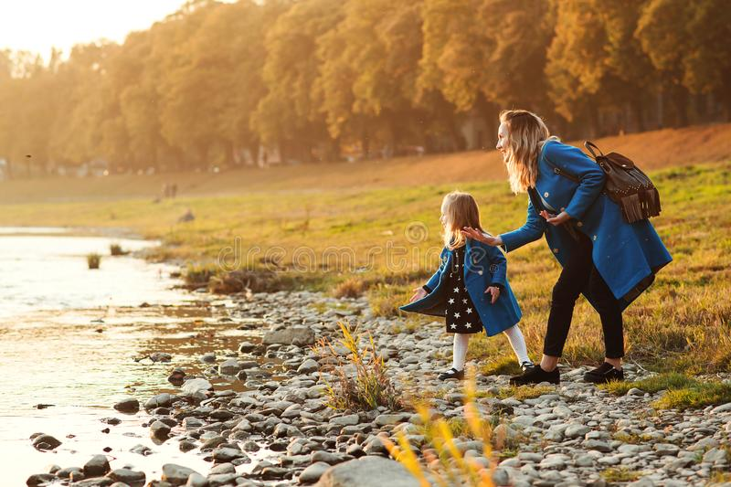 Mom with daughter in autumn. Mother and daughter walking near river in autumn time. Happy family. Fall weekend in the open air. Fa stock photo