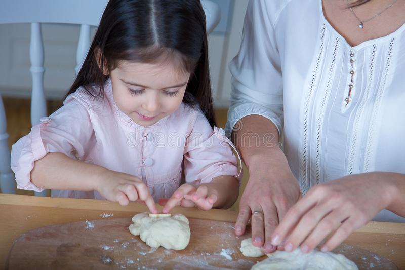 In the kitchen, mom and daughter bake cookies. Mom and daughter bake cookies. On the kitchen table are eggs,milk, dough royalty free stock image