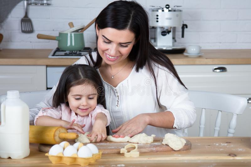 In the kitchen, mom and daughter bake cookies. Mom and daughter bake cookies. On the kitchen table are eggs,milk, dough stock photography