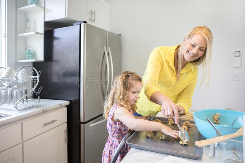 Mom and daughter baking cookies in their kitchen. A Mom and young daughter baking in their bright, modern kitchen royalty free stock photography