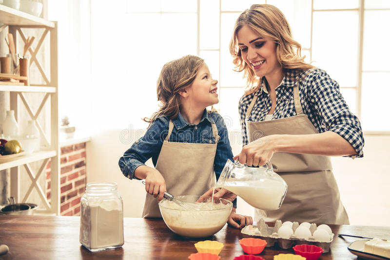 Mom and daughter baking. Cute little girl and her beautiful mom in aprons are smiling while preparing dough for muffins in the kitchen royalty free stock photo