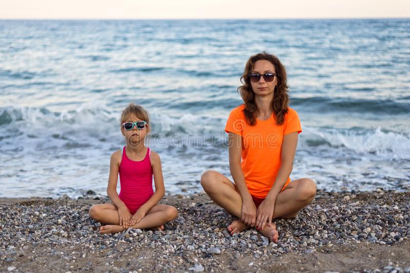 Mom and daughter on the beach, family vacation.Mom and daughter meditate on the beach stock photos