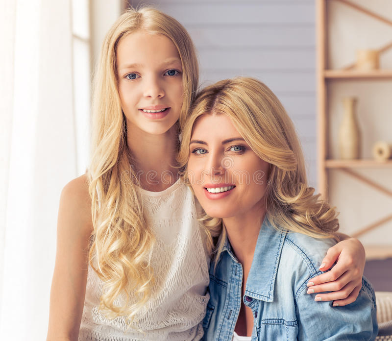 Mom and daughter. Beautiful blonde women and her teenage daughter are hugging, looking at camera and smiling while sitting at home royalty free stock image