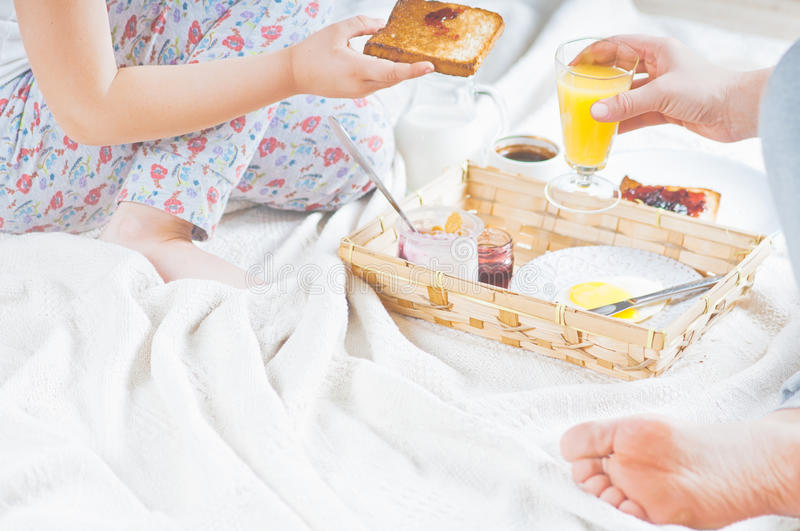 Mom and daughter breakfast in bed on a white blanket. A Mom and daughter breakfast in bed on a white blanket stock photo