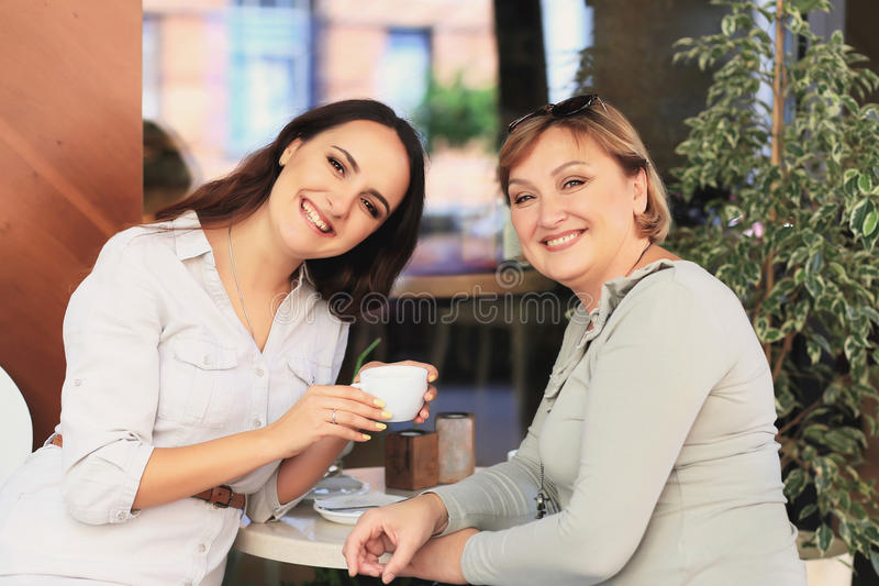 Mom and daughter are in the cafe. stock photos