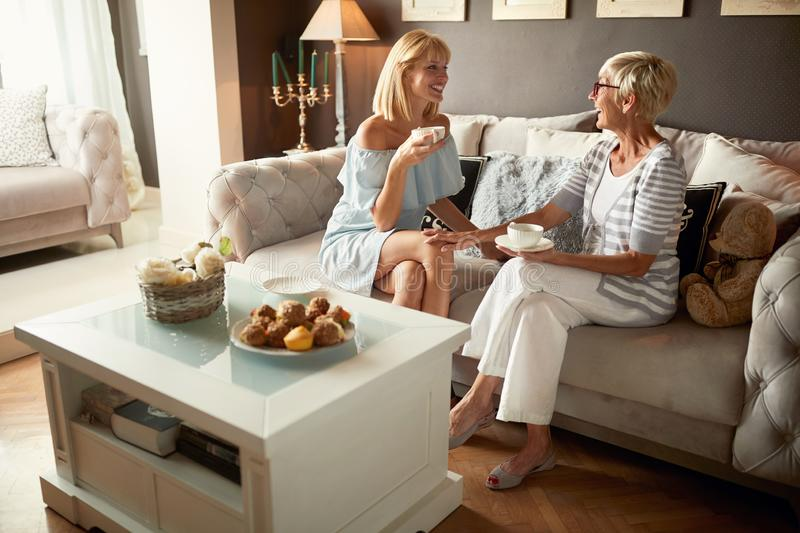Mom with daughter chatting and drinking coffee royalty free stock photography
