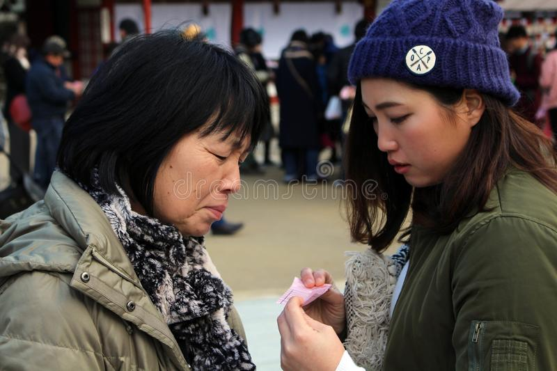 Mom & daughter checking the result of fortune-telling paper royalty free stock images
