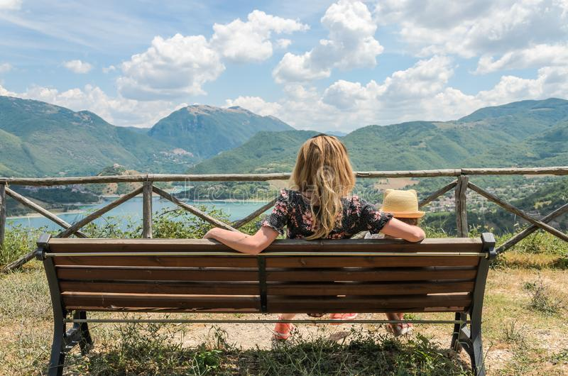 Mom and daughter child sitting on a bench and looking at a mountain landscape with a mountain lake royalty free stock photography