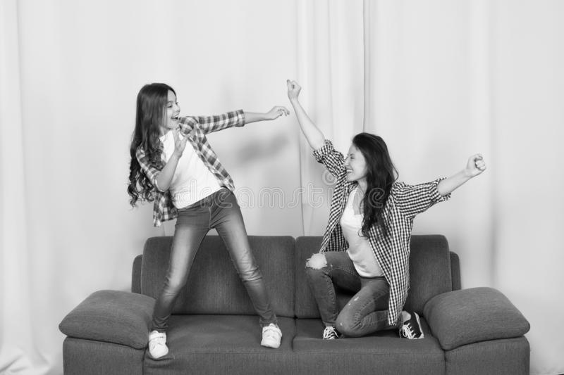 Mom and daughter close friends. Girlish team. Mother and cheerful daughter having fun on couch. Happy childhood. Girls royalty free stock photo