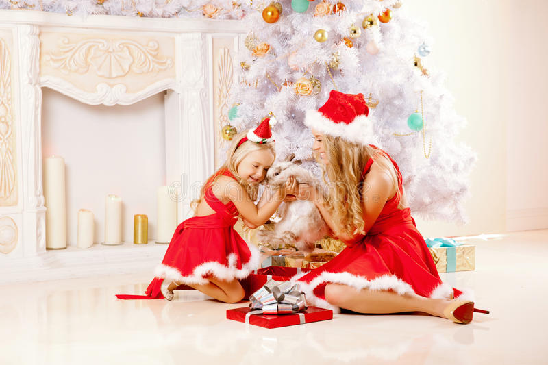 Mom and daughter dressed as Santa celebrate Christmas. Family at. Mother and daughter dressed as Santa celebrate Christmas. Family at the Christmas tree. Woman royalty free stock photos