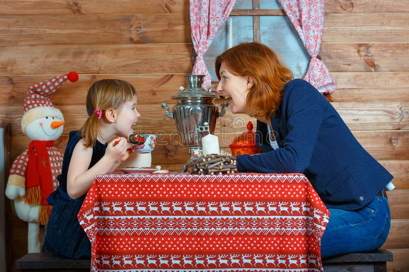Mom and daughter drink tea from a samovar and talk stock photo