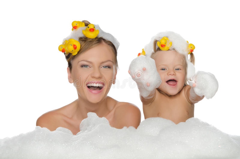 Mom and daughter with ducks in soap foam. Mom and daughter with ducks and soap foam isolated on white stock images