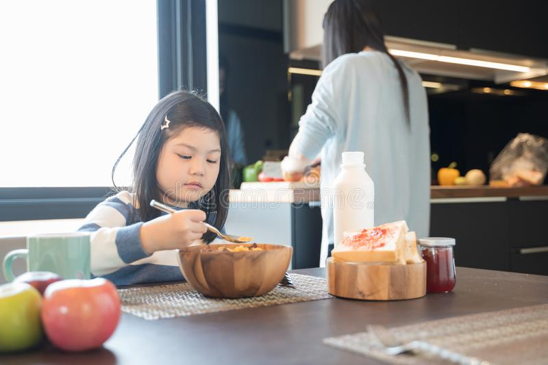 Mom and daughter eating Cereals with milk having breakfast in kitchen. royalty free stock image