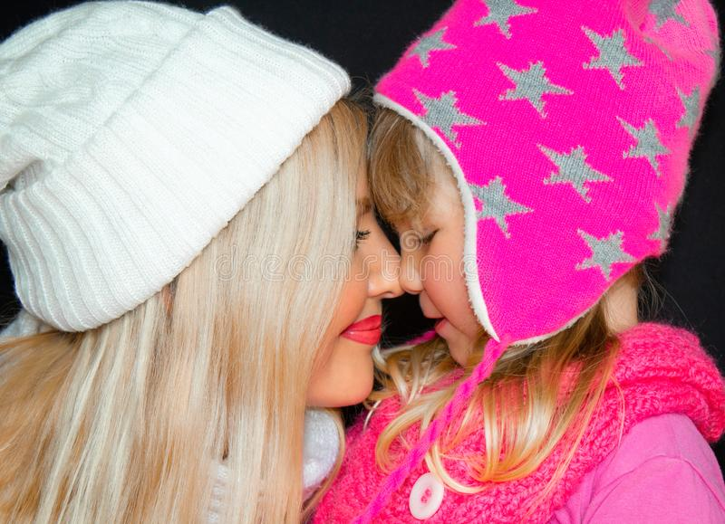 Mom and daughter embrace, in knitted hats, on a black background. Happy family, smiles and joy. royalty free stock image