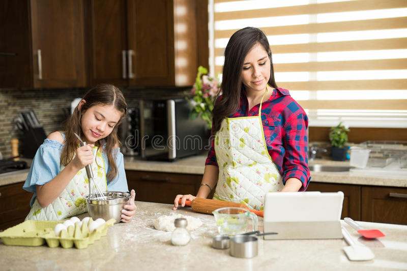 Mom and daughter following recipe royalty free stock photography