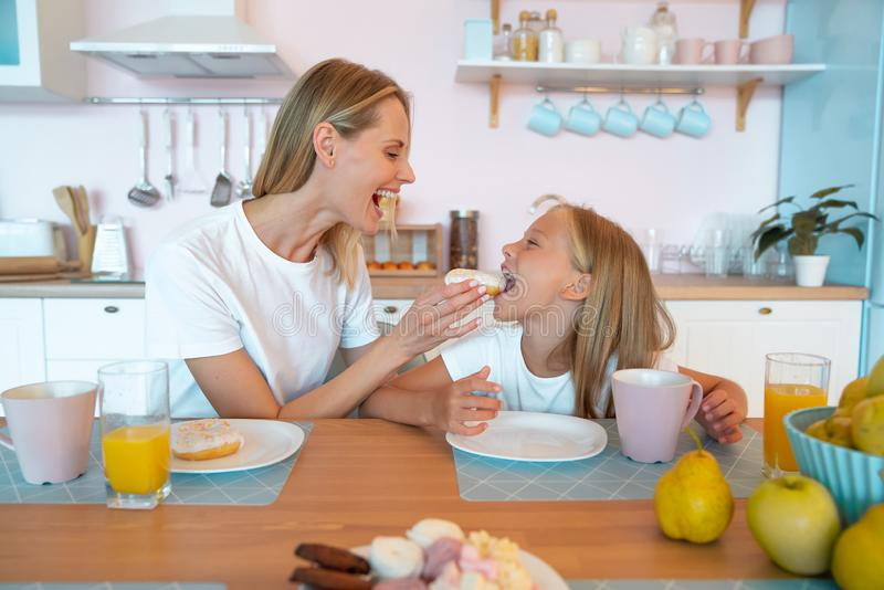 Mom and daughter are fooling around in the kitchen with donuts. cute family photo. dressed in white tshirts royalty free stock image