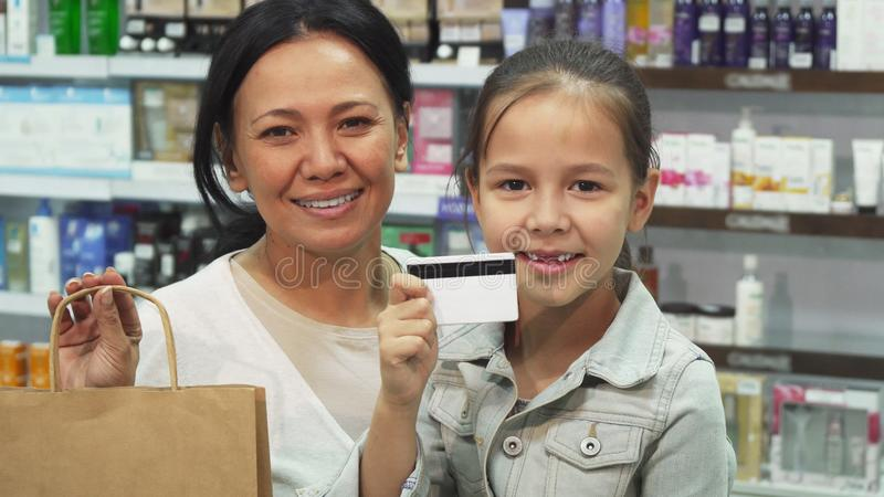 Mom and daughter have made purchases in the pharmacy with a credit card royalty free stock image