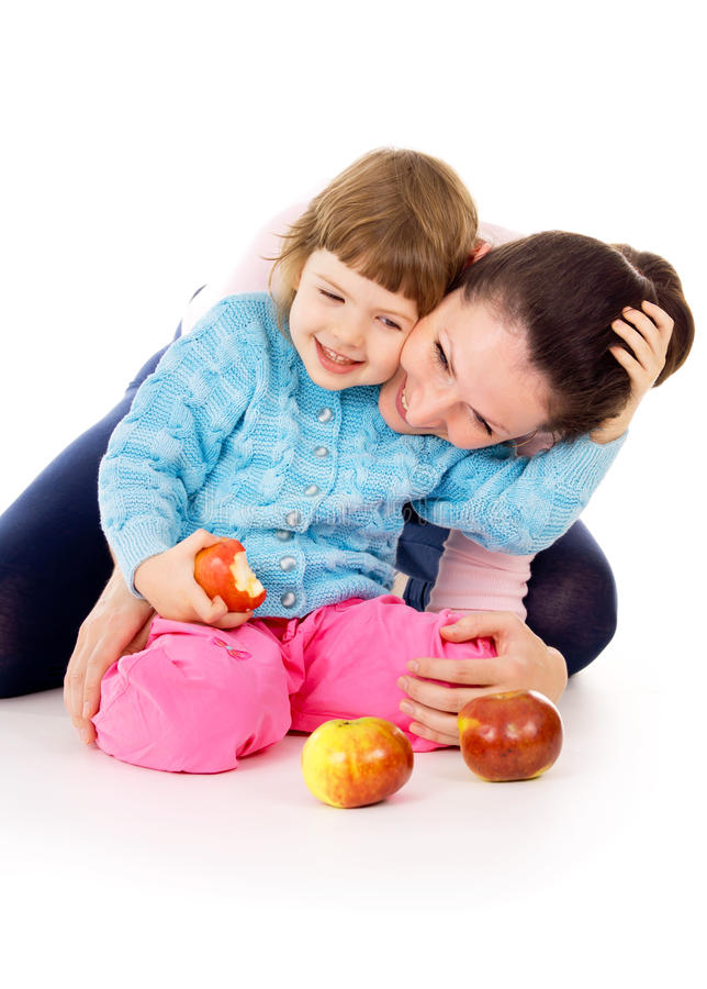 Mom with daughter having a healthy way of life, and eat apples royalty free stock images