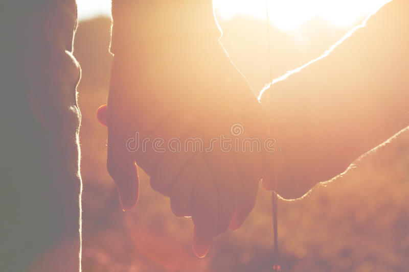 Mom and daughter are holding hands stock photo