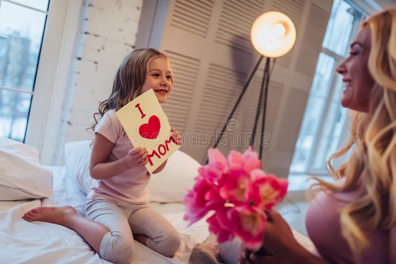 Mom and daughter at home. I love you, mom! Attractive young women with little cute girl are sitting on bed and spending time together at home. Mom is receiving stock image