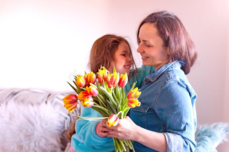 Mom and daughter are hugging on the sofa in the room, happy family. Tulips as a gift for mother`s day. Woman with flowers. Place stock image
