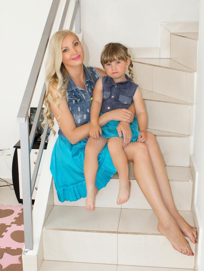 Mom and daughter in identical dresses are sitting on the stairs, blondes. royalty free stock image