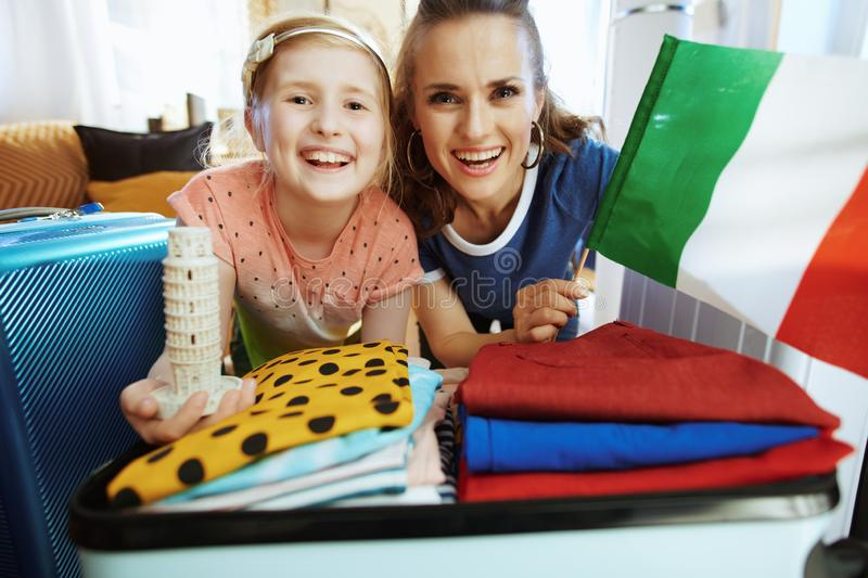 Mom and daughter Italian flag and Leaning tower souvenir. Happy trendy mother and daughter in the modern living room in sunny summer day Italian flag and Leaning royalty free stock photography