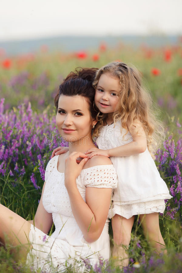 Mom and daughter on a lavender field. A beautiful young women ,a brunette,with her small daughter,a girl with long wavy,blond hair,both dressed in white dresses royalty free stock photography
