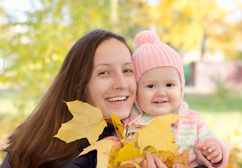 Mom and daughter with leaves stock images