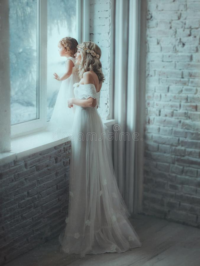 Mom and daughter are looking out the window, behind which a winter fairy tale opens. They have beautiful white dresses stock photo