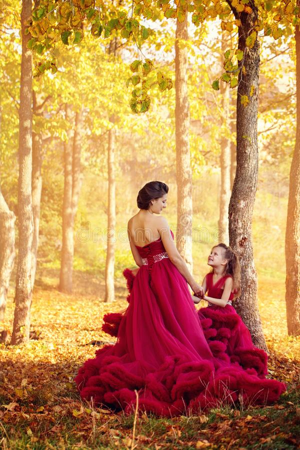 Mom and daughter in dresses. Mom and daughter in luxurious dresses in the autumn forest royalty free stock photo