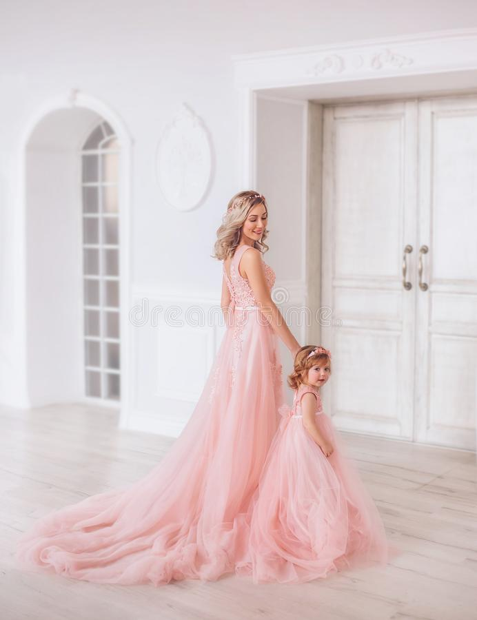 Mom and daughter in luxurious, pink dresses with a long train. Family clothes, identical dresses. The background is stock photo