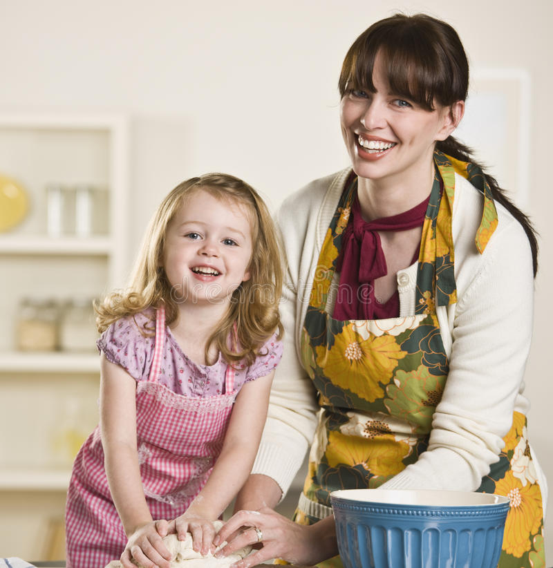Mom and daughter making bread. Brunette mom and blond daughter making bread on the kitchen counter, while wearing aprons. Both are kneading dough and looking at stock image