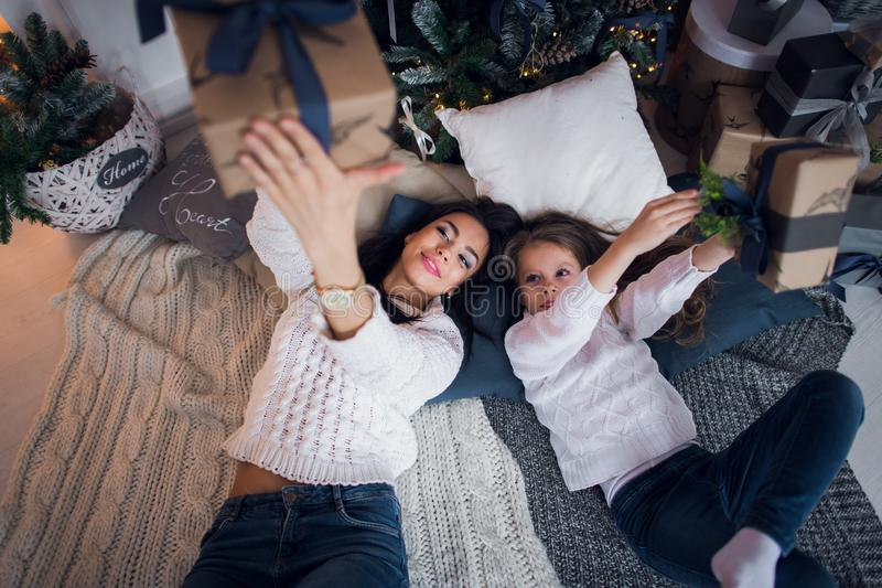 Mom and daughter meet a happy Christmas , family in a room with Christmas fir tree and gifts. Top view.  royalty free stock photos