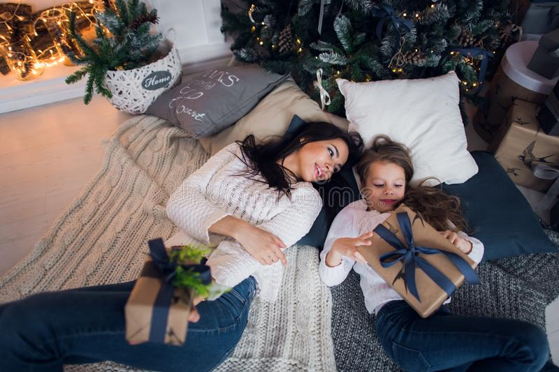 Mom and daughter meet a happy Christmas , family in a room with Christmas fir tree and gifts. Top view.  royalty free stock photo