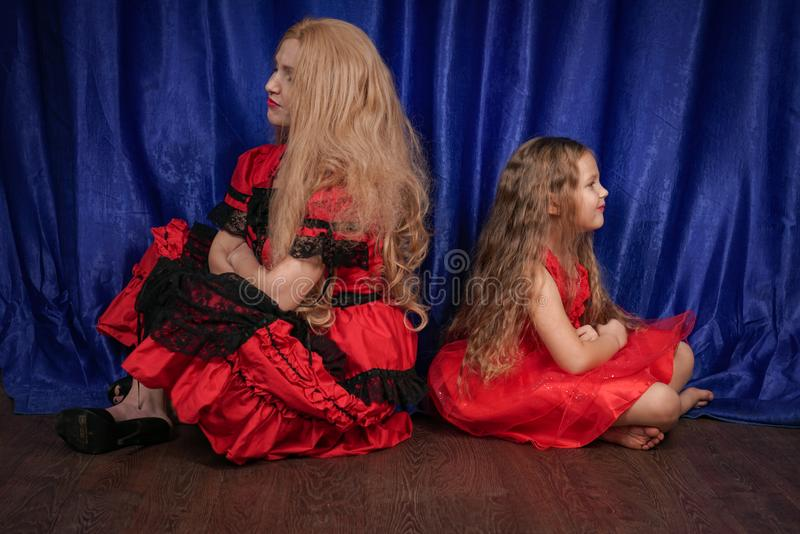 Mom and daughter are offended and sitting on the floor. mom is trying to establish peace and friendship with the child. Family stock photography