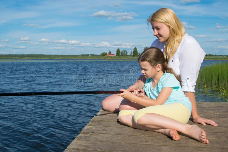 Mom and daughter on the pier, against the backdrop of a beautiful landscape, hold a fishing pole to catch fish, close-up, there is. A place for an inscription stock photos