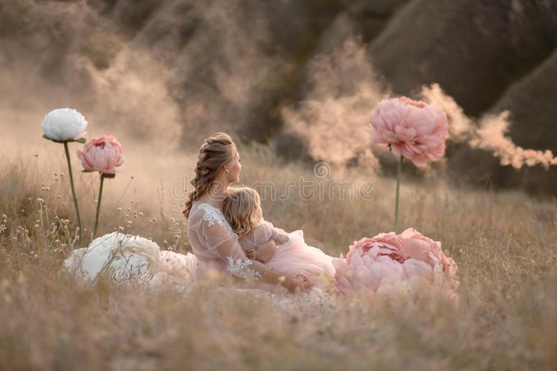Mom and daughter in pink fabulous dresses look into the distance, sitting in a field surrounded by large pink decorative flowers stock image