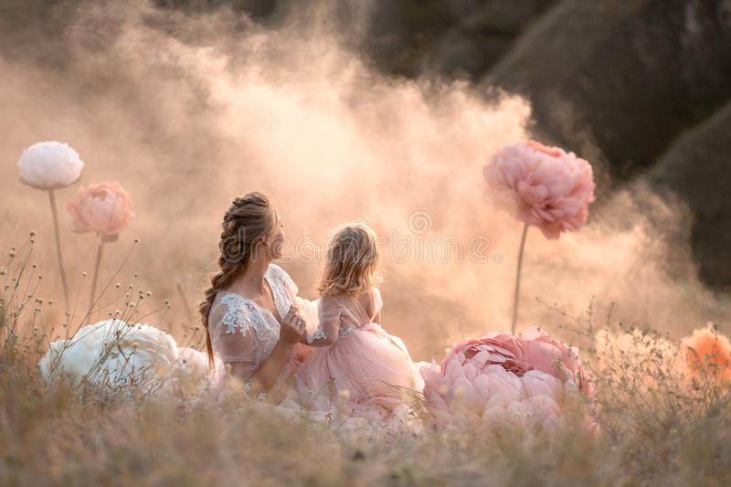 Mom and daughter in pink fabulous dresses look into the distance, sitting in a field surrounded by large pink decorative flowers royalty free stock photos
