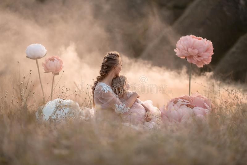Mom and daughter in pink fabulous dresses look into the distance, sitting in a field surrounded by large pink decorative flowers royalty free stock photo